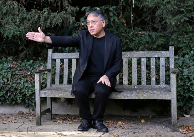 """British novelist Kazuo Ishiguro gestures during a press conference at his home in London on Oct. 5. Ishiguro, best known for """"The Remains of the Day,"""" won this year's Nobel Literature Prize."""