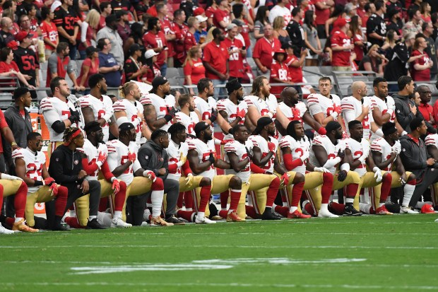 Members of the San Francisco 49ers kneel for the national anthem before the start of their game against the Arizona Cardinals on Sunday.