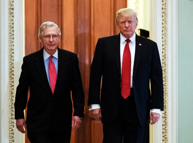 President Donald Trump, escorted by Senate Majority Leader Mitch McConnell, arrives on Capitol Hill to have lunch with Senate Republicans on Tuesday and push for his tax reform agenda.