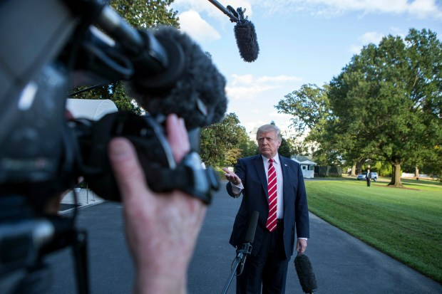 """President Donald Trump speaks with reporters outside the White House on Oct. 7. During the exchange, Trump called NBC News """"fake news"""" after it reported tension between the president and Secretary of State Rex Tillerson."""