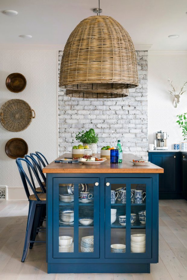 This 2017 photo provided by Scripps Networks, LLC shows a kitchen designed by Brian Patrick Flynn. The kitchen has bold navy cabinets contrasted with natural elements like exposed brick and natural woven light fixtures. (Robert Peterson, Rustic White Photography/Scripps Networks, LLC via AP)