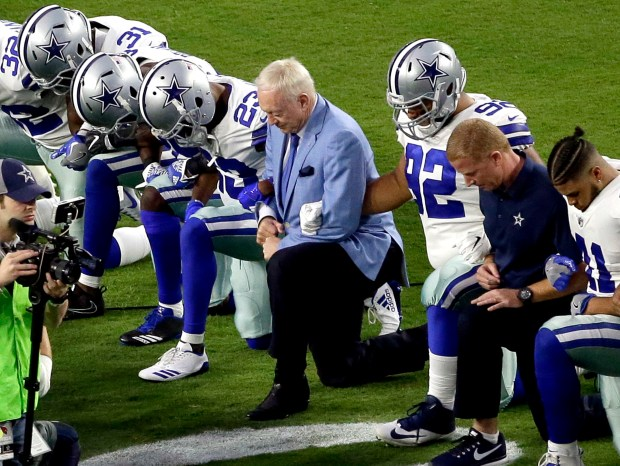 The Dallas Cowboys, led by owner Jerry Jones, take a knee prior to the national anthem before the Cowyboys Sept. 25 game against the Arizona Cardinals in Glendale, Ariz. Jones has since said players who don't stand for the anthem won't be allowed to play.