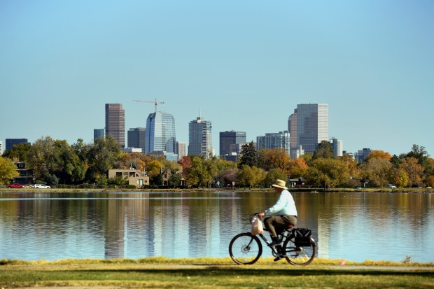 A cyclist rides past Sloans Lake with the Denver skyline reflected in the water.