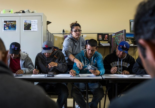 Mari Medrano, human resources director at CoCal Landscape, helps temporary migrant workers fill out paperwork in Denver.