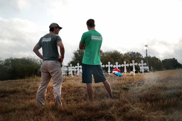 On Tuesday, two men view a memorial for the 26 people who were killed Sunday at a church in Sutherland Springs, Texas.