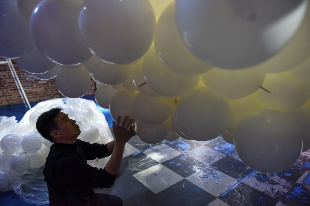 HongSeok Goh works on an art installation made entirely of balloons at the American Visionary Art Museum in Baltimore; Goh built the elephant and turtle sculpture, which is more than 20 feet long, with a team of six balloon artists who came with him from South Korea and two American balloon artists.