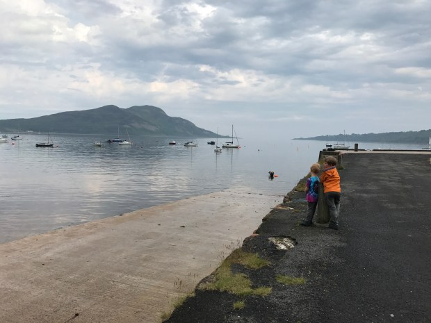 The author's sons watch boats come and go from a dock in the village of Lamlash on the Isle of Arran, passengers depart on sail boats as well as a small ferry that takes visitors to the nearby Holy Island, in the distance.