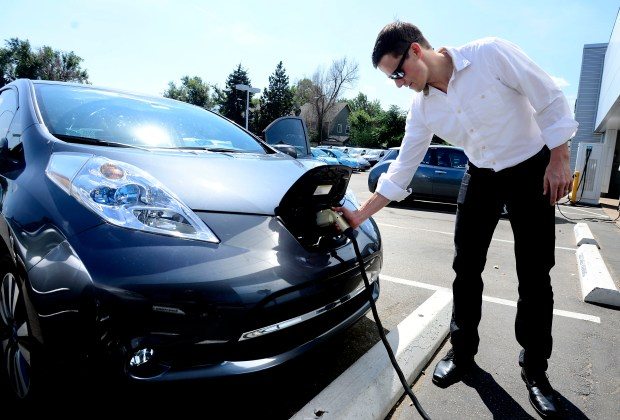A man unplugs his Nissan Leaf electric vehicle after charging it at a dealership in Boulder on Sept. 11, 2015.