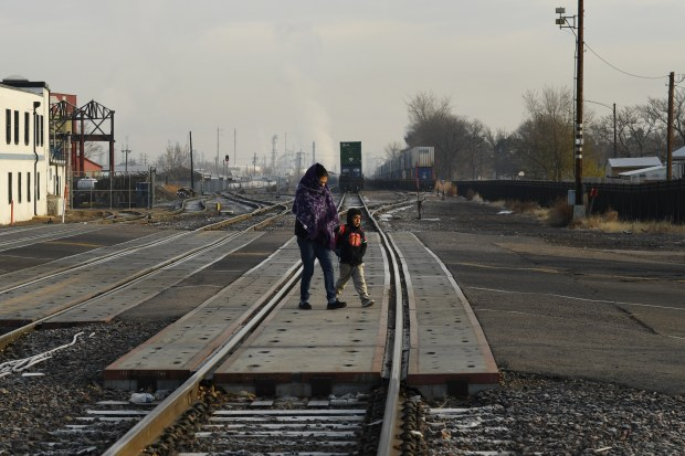 DENVER, CO - OCTOBER 10: A women and child walk over railroad track at 47th Ave. and York St. on the way to Swansea Elementary School November 10, 2017 in Denver, Colorado. Denver voters recently passed a bond package which plans to build a bike and pedestrian bridge to traverse train tracks. (Photo by RJ Sangosti/The Denver Post)