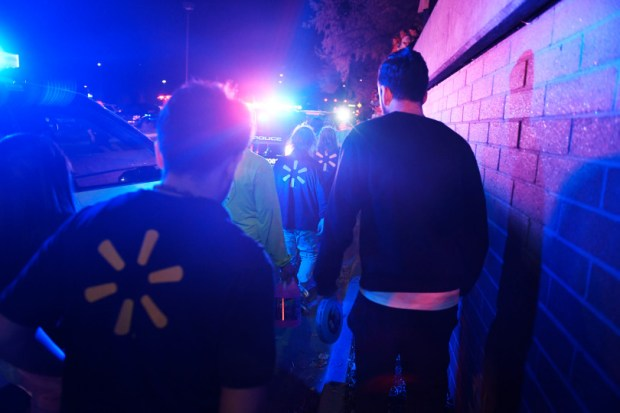 Employees exit the parking lot of a Thornton Walmart last Wednesday after a gunman shot and killed three people before fleeing.