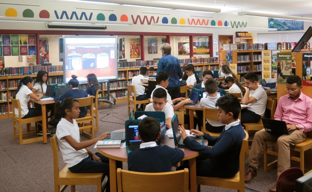 In this Sept. 27, 2017 photo students learn about searching for books and keeping track of what they've read in the library at Bruce-Guadalupe Community School, a charter school in Milwaukee. Charters are over-represented among schools where minorities make up the vast majority of the student body, according to an analysis of enrollment data nationwide by The Associated Press. Bruce-Guadalupe is 97 percent Latino.