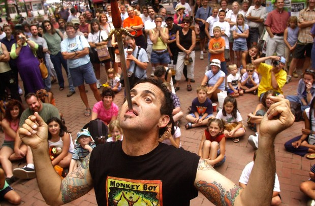 Street performer Johnny Fox entertains a crowd with his sword swallowing-act on Aug. 7, 2002, on Boulder's Pearl Street Mall. Fox, 64, died earlier this month from liver cancer.