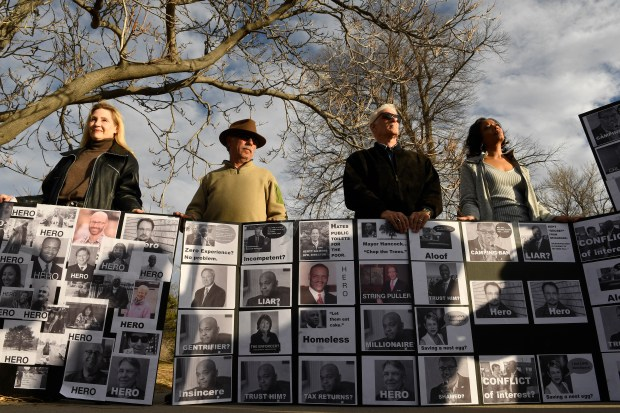 "From left to right Jackie Victor, Louis Plachowski, Keith Loftin and Lisa Claderon hold up signs during a rally near City Park on Dec. 3, 2017, in Denver. A group from City Park Friends and Neighbors organized a rally to ""reclaim our city"" and to protest the city's decision to cut down over 260 trees in City Park. The removal of the trees is part of the city's plan to use the golf course as a drainage project that is part of the city's larger Platte to Park Hill stormwater plan. The golf course was closed in November and will be closed entirely for up to two years. Some see the reconfiguration of City Park Golf Course as a thinly veiled subterfuge to pave the way for new construction plans on I-70 and along the I-70 corridor.(Photo by Helen H. Richardson/The Denver Post)"