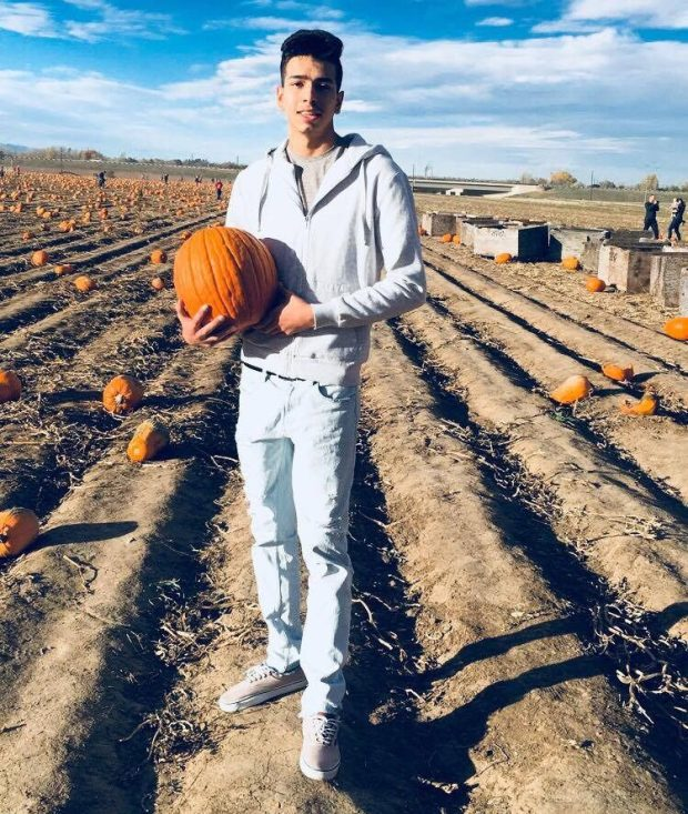 image of the victim (provided by his family). Kyler Grabbingbear (wearing light blue jeans and a light blue hoodie) is standing amid a somewhat bare pumpkin patch while holding a pumpkin in his right arm.