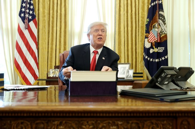 President Donald Trump talks with journalists after signing tax reform legislation into law in the Oval Office on Dec. 22.