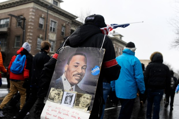 Bob Kirtdoll carries a poster on his back as he marches in the Marade during the 32nd annual Martin Luther King Day celebration on Monday in Denver.