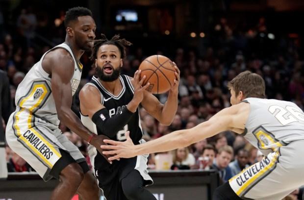 San Antonio Spurs' Patty Mills, center, ...