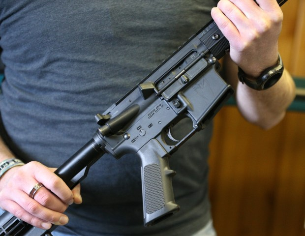 A man displays an AR-15, the same type of weapon used in the Florida school shooting, at a gun shop in Orem, Utah, on Thursday.
