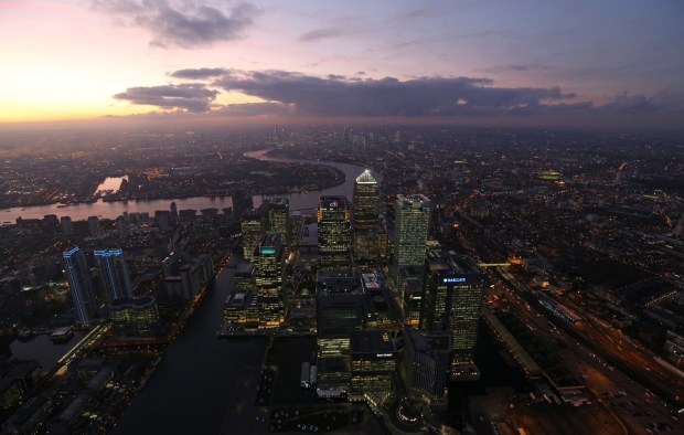 No. 1 Canada Square stands surrounded by the offices of global financial institutions in this aerial photograph looking west along the River Thames toward the City of London from Canary Wharf business and shopping district in London.