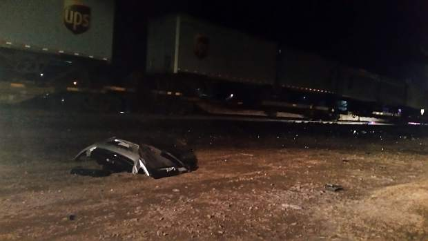 The bumper of a car rests near railroad tracks Tuesday night in Eaton.