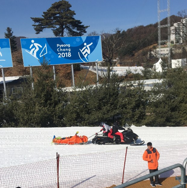 Team Canada's Chris Del Bosco of Vail waves to the crowd as he is hauled in a medical sled to the waiting helicopter after a brutal crash in Wednesday's Olympic ski cross contest at Phoenix Park in Bongpyeong, South Korea. Photo by Jason Blevins / The Denver Post.