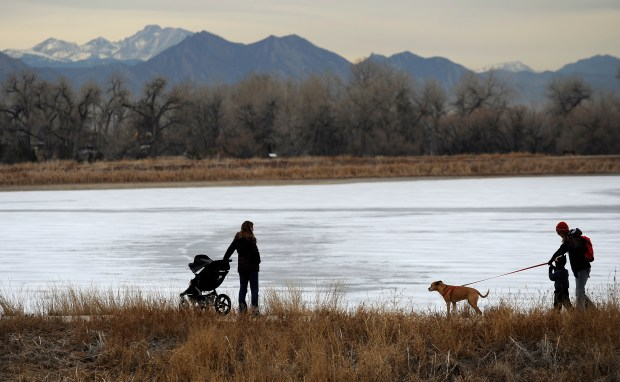 Families walk around Crown Hill Lake, which is at the border of Lakewood and Wheat Ridge, Thursday, Jan. 10, 2013.