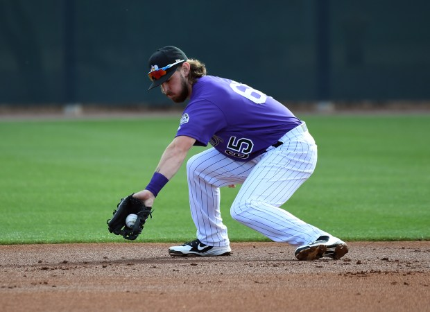 Colorado Rockies Brendan Rodgers (65) backhands ...