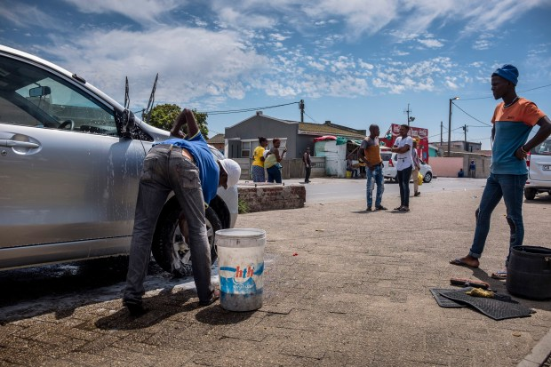 Akena Dubanga, who owns a car wash in Gugulethu,about 10 miles from Cape Town, South Africa, says it now uses buckets rather than hoses to use less water per car. Workers are shown Feb. 14, 2018.