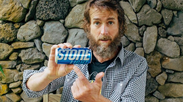 """Stone Brewing Co. founder and chairman Greg Koch holds a can of Keystone Light beer. The California brewer is suing MillerCoors for infringement over the emphasis of """"Stone"""" in marketing Keystone."""