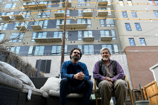 Neighbors Tim Oldham, left, and Carlos Santisteven, right, sit in the shadow of a huge new building in Oldham's backyard at 2555 Glenarm Place on March 13, 2018 in Denver. The two neighbors live across the street from each other and both have been impacted by this huge 8-story commercial and residential building that's going up in the 2500 block of Welton Street.