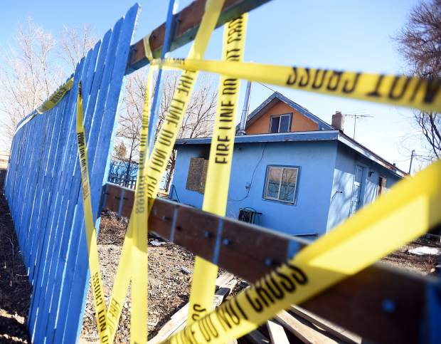 Crime tape surrounds a home Thursday in Gill after a fatal fire. Fire investigators with the Platte Valley Fire Protection District are investigating the fire that caused only minimal damage to a two-story house in the area of 6th Avenue and 4th Street.