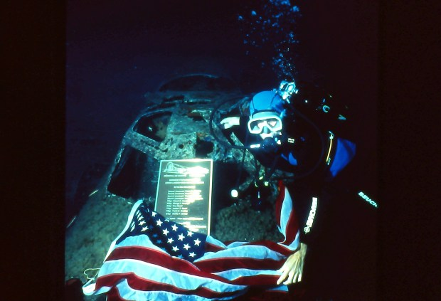 John Christopher Fine underwater posing with a memorial plaque on a sunken B-17 with the American flag in 1995 in the Bay of Calvi, in the Mediterranean Sea off the coast of the French island of Corsica.
