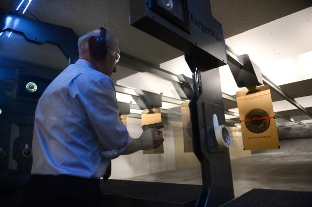 U.S. Rep. Mike Coffman, R-Aurora, shots a 9mm Glock at the grand opening of the Centennial Gun Club in Centennial, Colo., on Feb. 20, 2014.