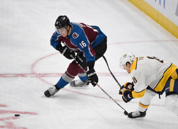Colorado Avalanche defenseman Nikita Zadorov (16) eyes the puck under pressure from Nashville Predators center Kyle Turris (8) in the second period during the third game of round one of the Stanley Cup Playoffs at Pepsi Center on April 16, 2018.