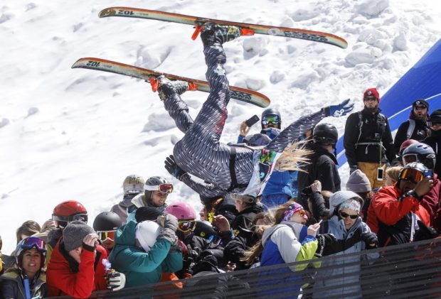 A participant of the Red Bull Slopesoakers Pond Skimming competition, Hayden Wright, 26, flies crowd from the jump during the event Saturday, April 14, 2018 at Copper Mountain.