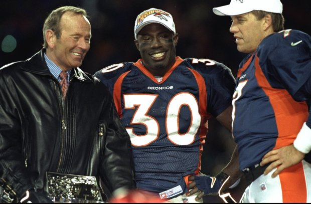 Terrell Davis (30) of the Denver Broncos stands with Broncos owner Pat Bowlen, left, and John Elway (7) after winning the AFC Championship Game against the New York Jets at Mile High Stadium in Denver on Jan. 17, 1999.