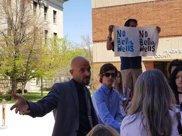 Jason Flores-Williams, left, defense attorney for Cullen Lobe, right, addresses a crowd Tuesday afternoon outside the Weld County Centennial Center, 915 10th St. in Greeley. The crowd arrived to support Lobe in his criminal trial, in which he is charged with misdemeanor trespass.