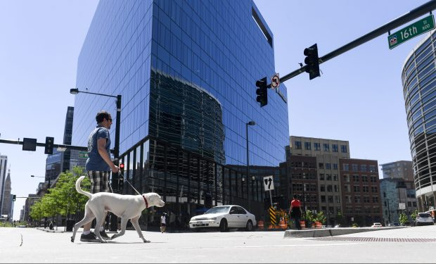 Tom McGean walks his dog, Ghost, near 16th and Wewatta streets on May 17, 2018. An estimated 1,700 dogs will soon live in the Union Station and Riverfront Park areas, between Union Station and Commons Park. This has caused some problems, including dead plants and trees as dogs with nowhere else to go relieve themselves in the few green spaces that exist.