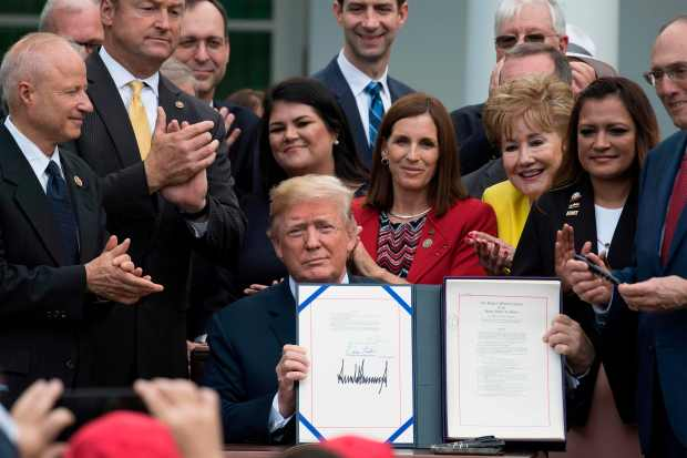 US President Donald Trump signs the ...