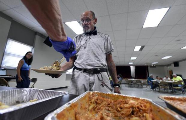 Curtis Cramer, who is experiencing homelessness, gets a serving of food during a communal meal provided by the Homeless Outreach Providing Encouragement program at the Heart of Longmont Church in July. Some nearby residents blame the church for drawing a group of transient homeless people have started living in Athletic Field Park, which is across the street.