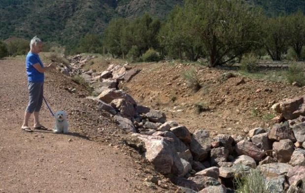 Dawson Ranch resident Judy Repass talks about the West Corridor Ditch located next to her home that was filled with running water, strong enough to move some of the boulders, during the July 23 hailstorm and flood. The city has added boulders to serve as barriers and slow the water, but more work needs to be done.