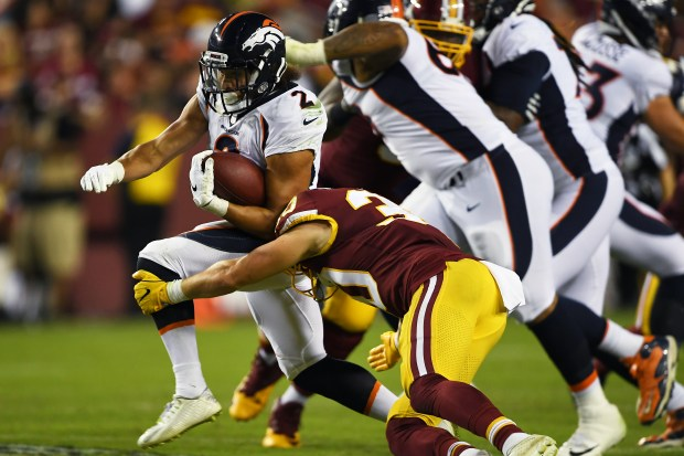 Running back Phillip Lindsay (2) of the Denver Broncos picks up yardage against the Washington Redskins at FedExField stadium in Landover, Md., on Aug. 24, 2018.