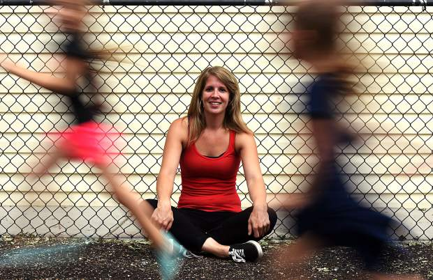 Lindsey Minne sits by the playground as her daughters run by on Wednesday at #1 Child Enrichment Center, 4601 9th St. in Greeley.