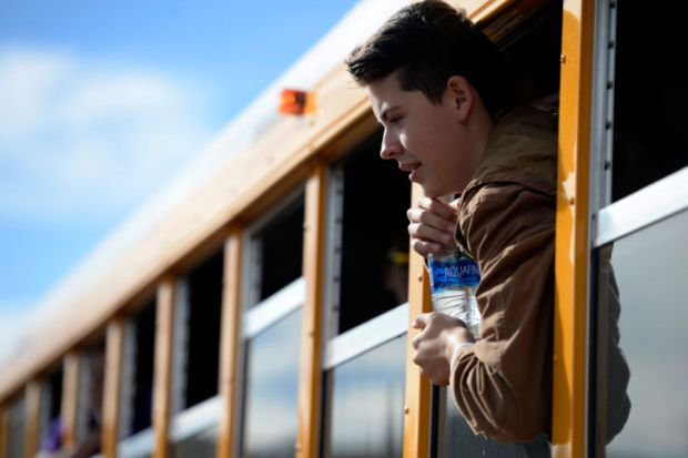 Haylen Orgunez, 14, hangs out the window of one of the new compressed natural gas buses as he poses for a group photo at Douglas County High School in Castle Rock, Colorado on November 16, 2016.