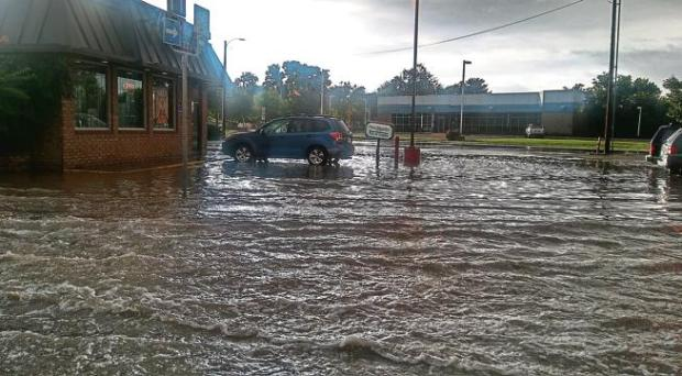 Stormwater floods a parking lot at 16th Street and U.S. 50 during a heavy rainfall July 23.