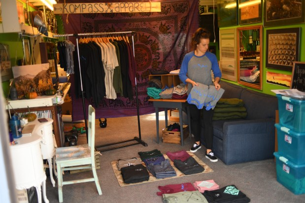 Kompass Apparel founder, owner, and sole employee Kynsi Saye works doing inventorying at her office,