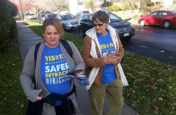 Sunshine Benoit, left, and Barbara Donachy, walk through Denver's Park Hill neighborhood to talk to voters about Proposition 112.
