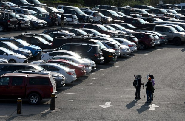 Hikers stand in the full parking ...