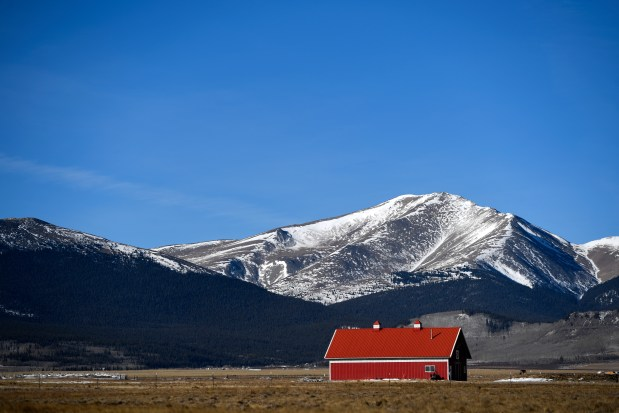A light dusting of snow sits atop the mountains behind a red barn