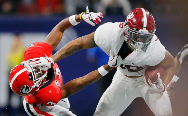 Irv Smith Jr. (82) of the Alabama Crimson Tide stiff arms Tyson Campbell (3) of the Georgia Bulldogs in the first half during the 2018 SEC Championship Game at Mercedes-Benz Stadium on Dec. 1, 2018 in Atlanta.